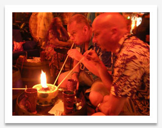 Two gents sipping from a flaming tiki bowl with long straws