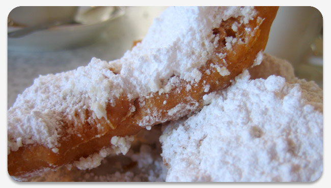 beignets covered in a snowfall of powdered sugar